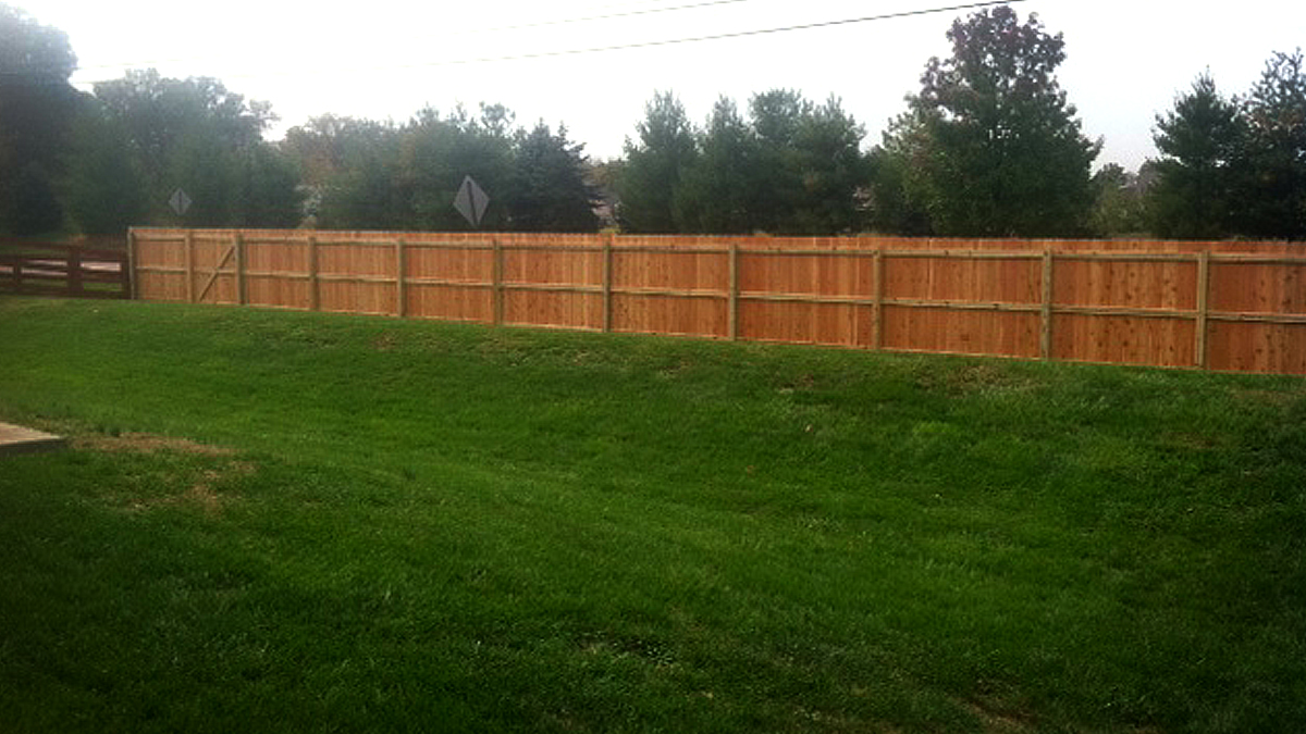 Block noise and prying eyes with a wood privacy fence from Ashlee Fence.